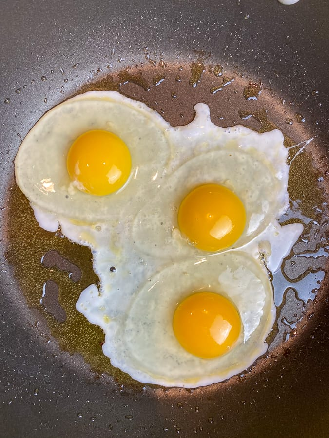 Three eggs broken in a skillet