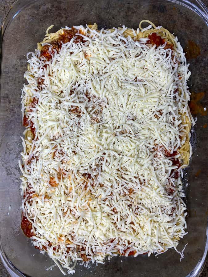 Mozzarella cheese sprinkled on sauce, sausage and spaghetti