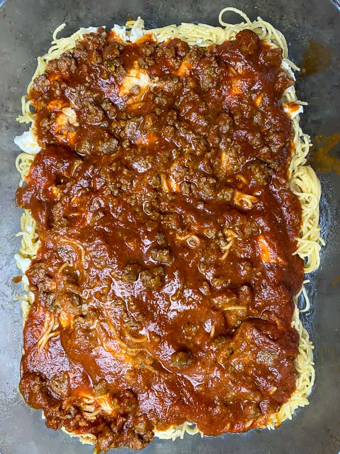 Layer of sausage and pasta sauce on baked spaghetti