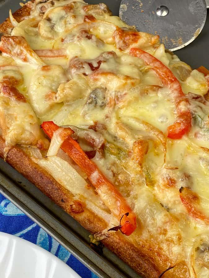 Monterey Jack cheese melted on fajita toppings on an easy fajita pizza