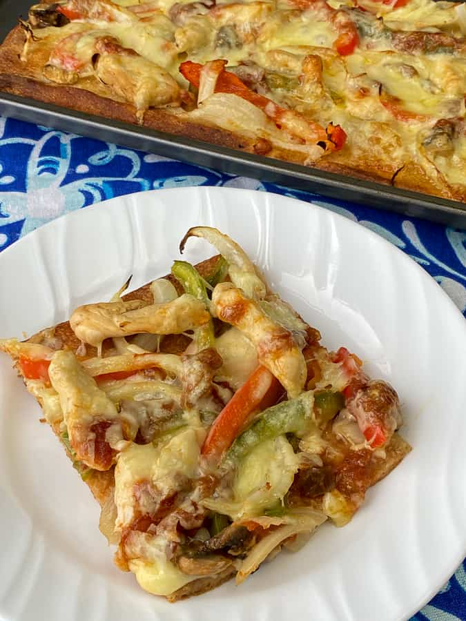 Red and green peppers, onions and mushrooms on refrigerated pizza crust to make a piece of Fajita Pizza.