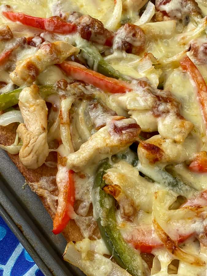 Melted cheese on sliced peppers, onions and chicken strips.