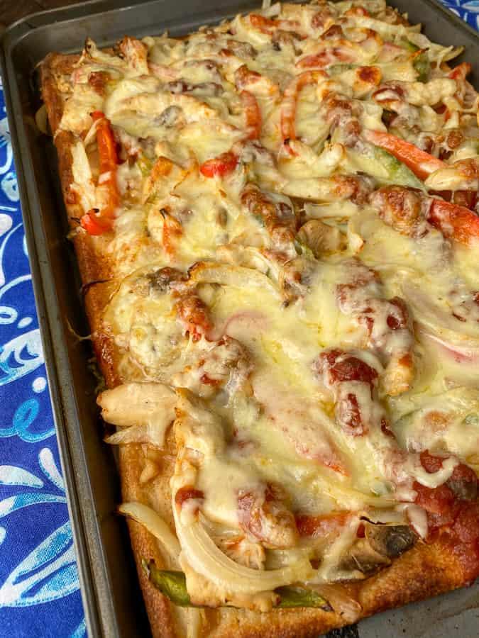 Warm baked fajita pizza on a baking sheet and blue napkin