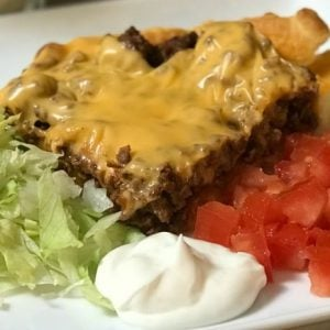 Slice of taco pie with crescent roll crust with lettuce, sour cream and tomatoes