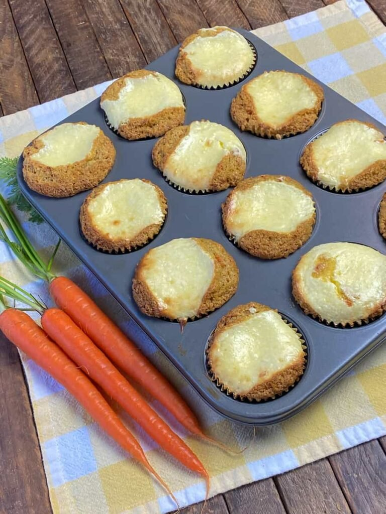 Sweet cream cheese filling in the center of carrot cake muffins in a muffin tin next to fresh carrots