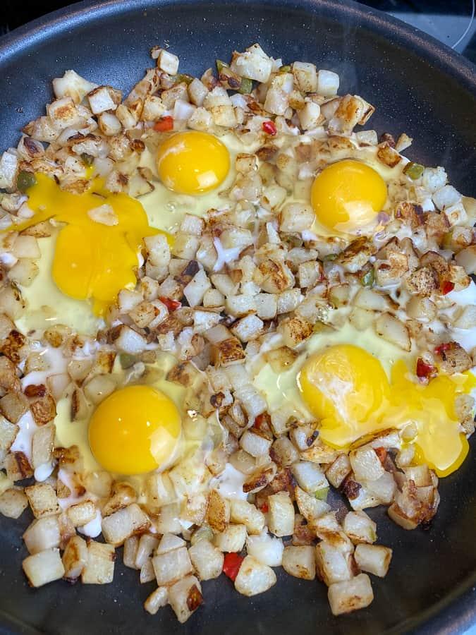 Eggs cracked in holes in hash brown breakfast skillet