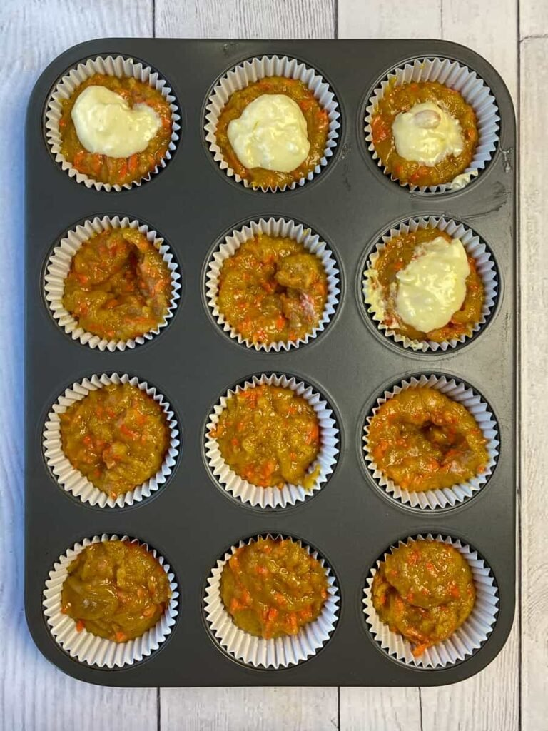 Muffin tin filled half full with carrot batter and adding cream cheese filling