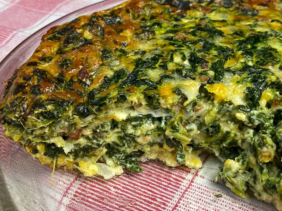 Serving dish of easy spinach and bacon quiche with melted cheese and lots of spinach