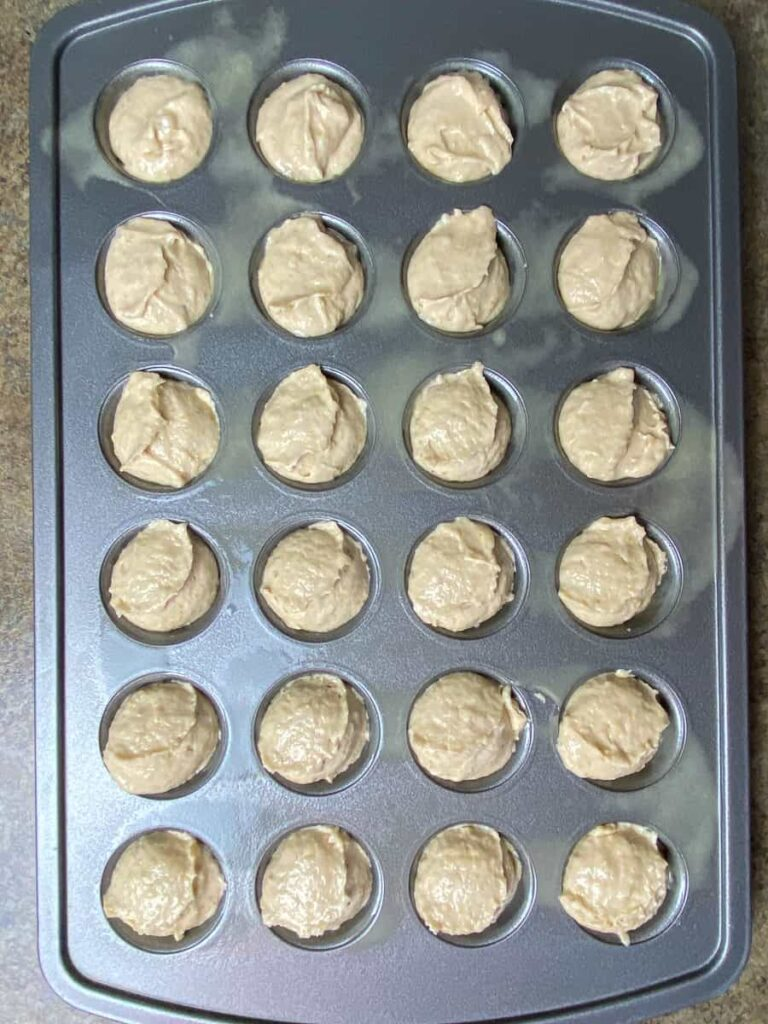 Large cookie scoop of batter in mini muffin tin
