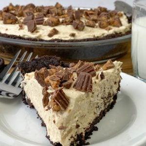 Slice of Oreo peanut butter pie next to full pie