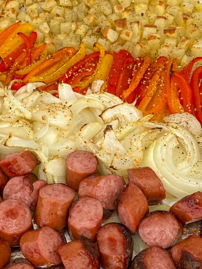 Close up Kielbasa with onions, peppers and potatoes on a sheet pan