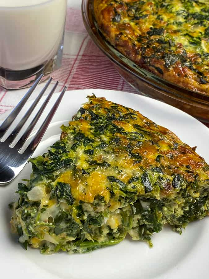 Delicious and creamy slice of spinach bacon quiche on a white plate