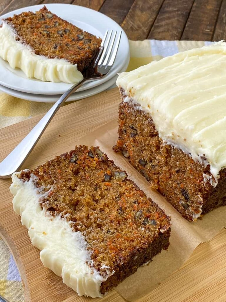 Carrot cake made in loaf pan on a cutting board next to slice on a plate