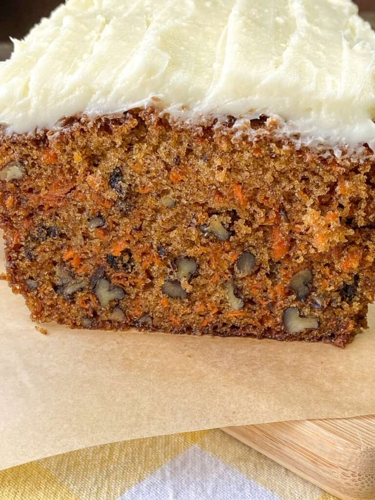 Moist carrot cake loaf sliced in half with frosting