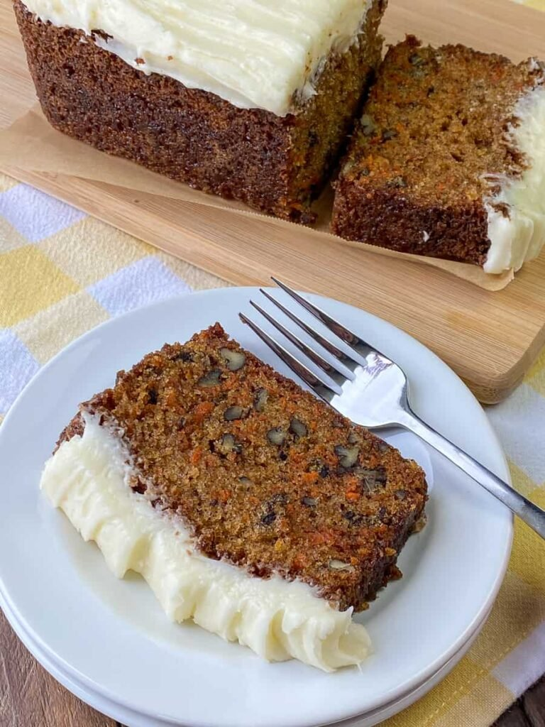 Slice of carrot cake loaf on a plate with fork
