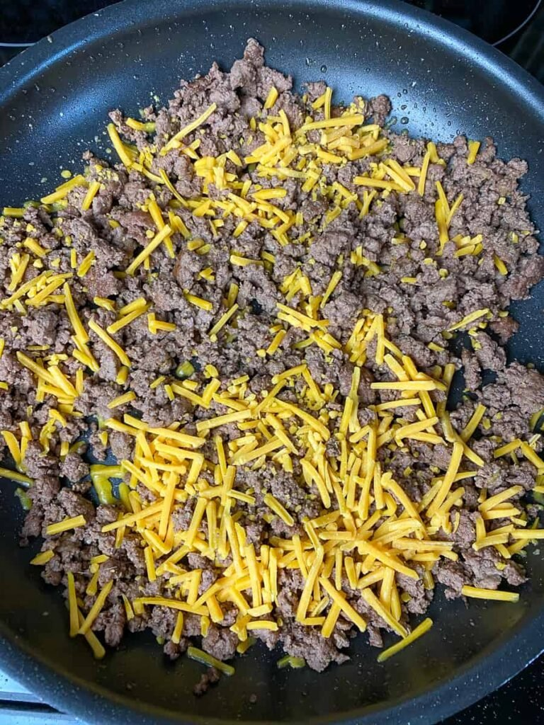 Skillet of cooked ground beef with shredded cheddar cheese