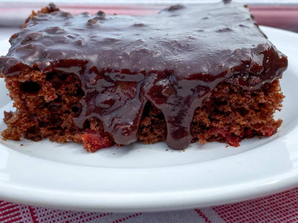 Rich frosting running over chocolate cake mix with cherry pie filling