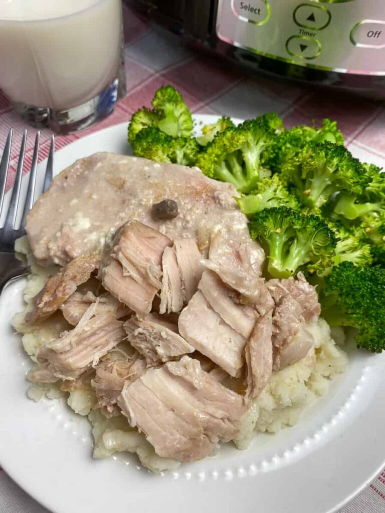 Shredded pork chop on mashed potatoes by broccoli on plate