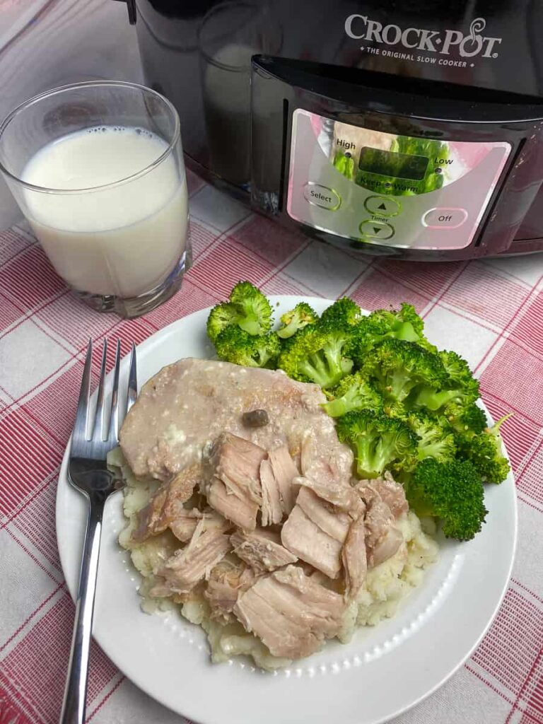 Crock pot pork chops with gravy on plate with fork