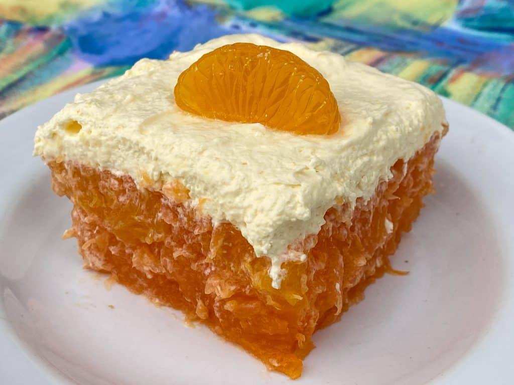 Thick piece of orange jello salad with mandarin oranges