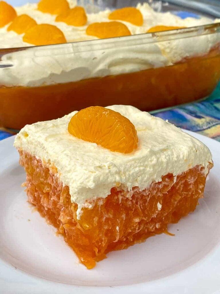 Mandarin orange on top of cool whip layer on orange Jello salad