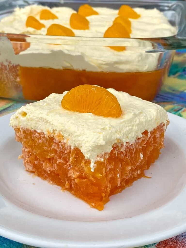 Dish of orange gelatin salad with a slice out front on a white plate