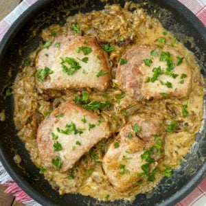 Skillet of smothered pork chops with fresh parsley