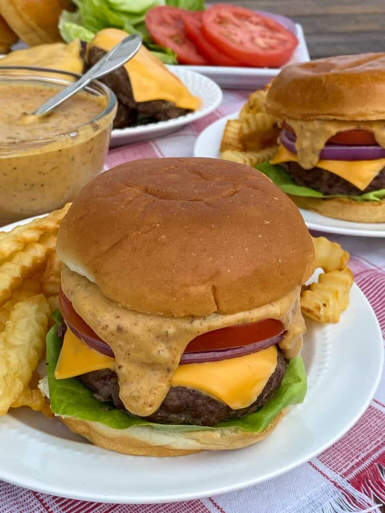 Burger sauce running down the side of a grilled hamburger on a brioche bun
