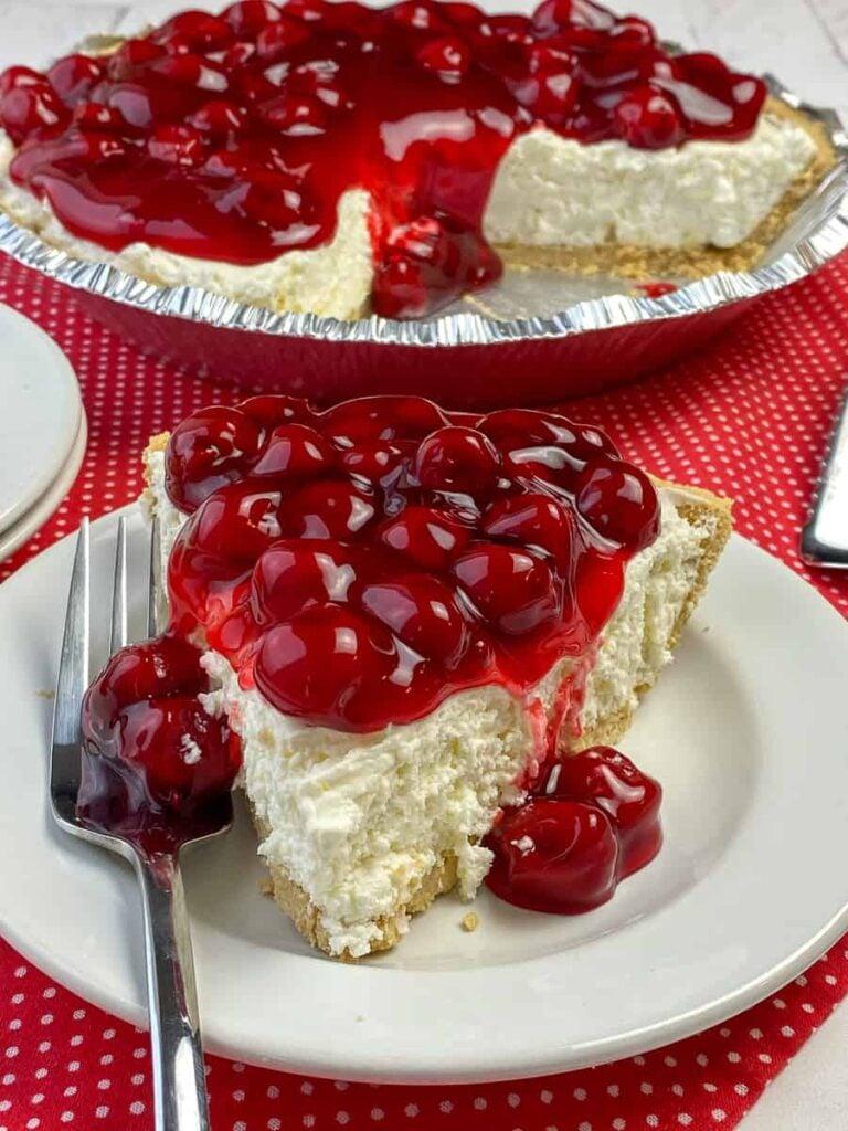 Slice of easy cherry cheesecake pie next to entire pie