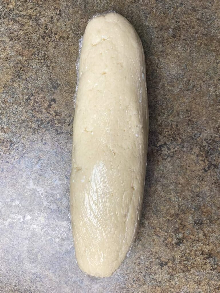 Refrigerated roll of cookie dough wrapped in plastic wrap