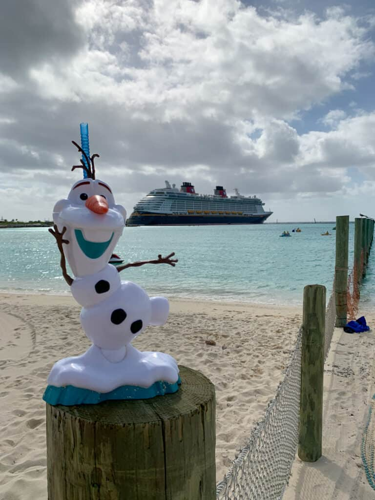 Olaf drink cup on a post in with Disney Dream cruise ship in the background