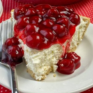 Slice of easy no-bake cheesecake recipe covered with cherry pie filling