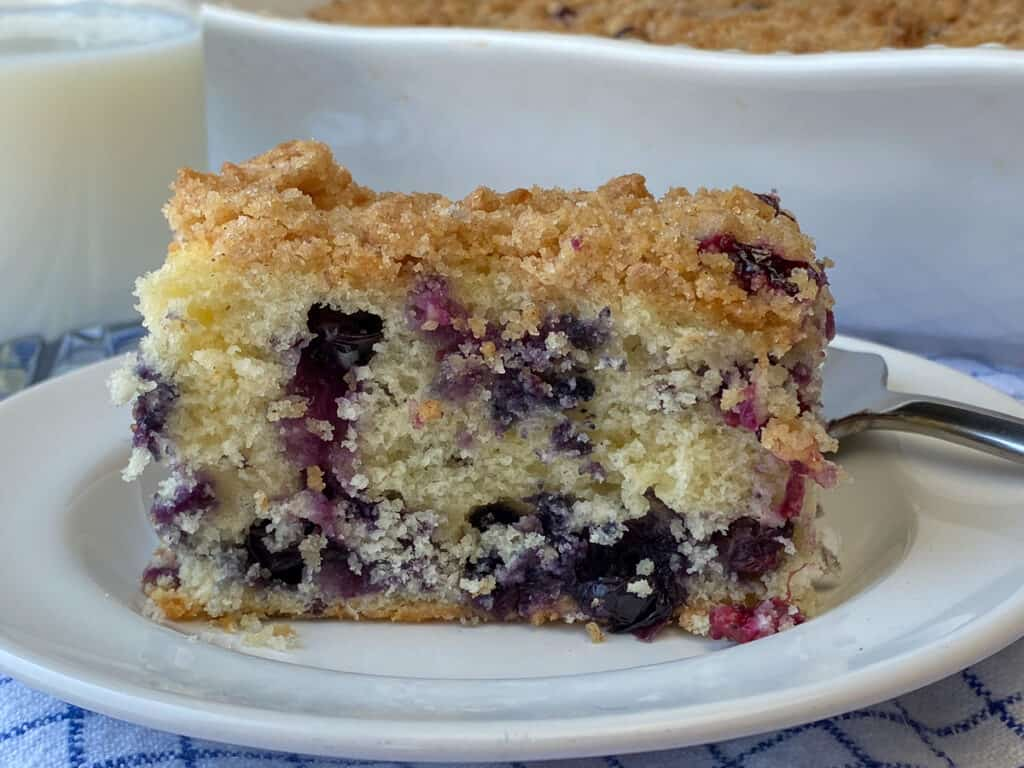 Piece of blueberry buckle on a plate by a glass of cold milk