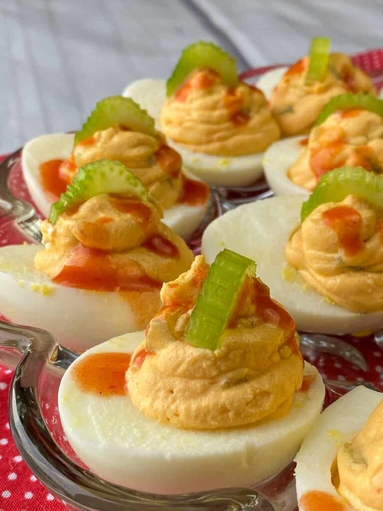 Deviled eggs drizzled with hot sauce and slices of celery
