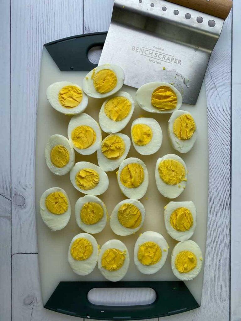 Using bench scraper to slice boiled eggs in half