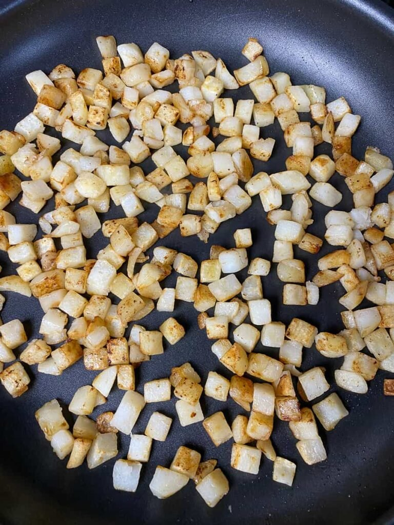 Fried potato cubes in a skillet