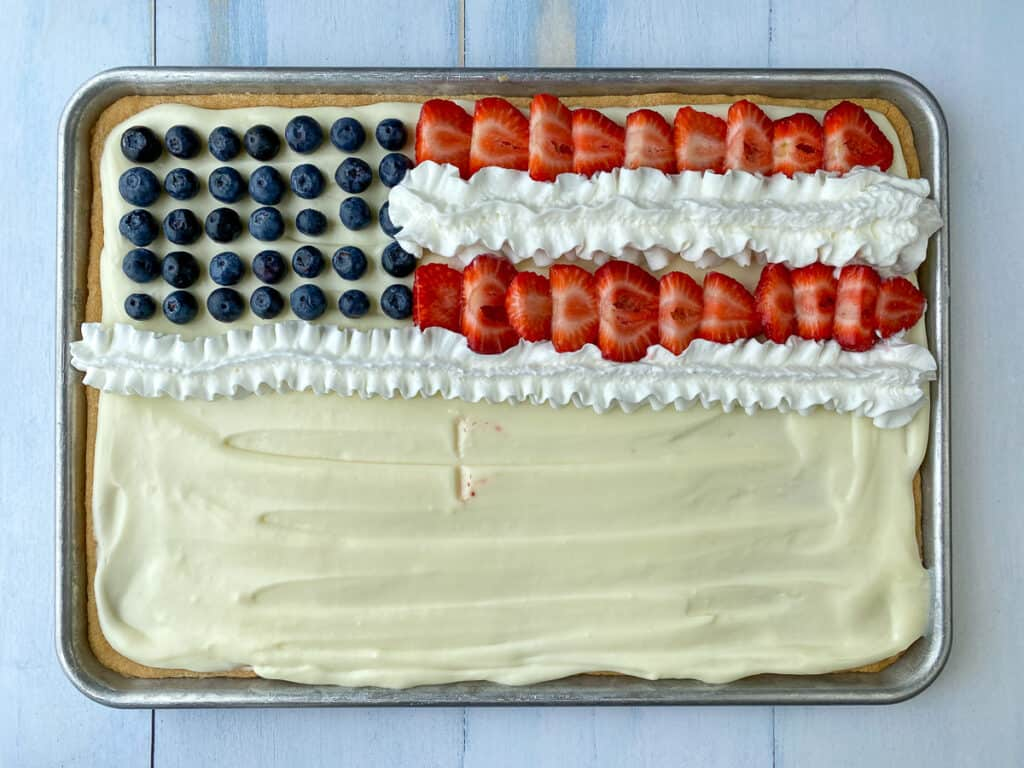 Rows of strawberries and whipped cream to represent stars and stripes on American flag fruit pizza