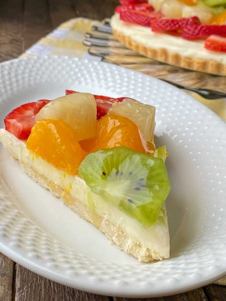 Slice of fruit pizza with sugar cookie crust, cream cheese frosting, a variety of fruit and a sweet glaze