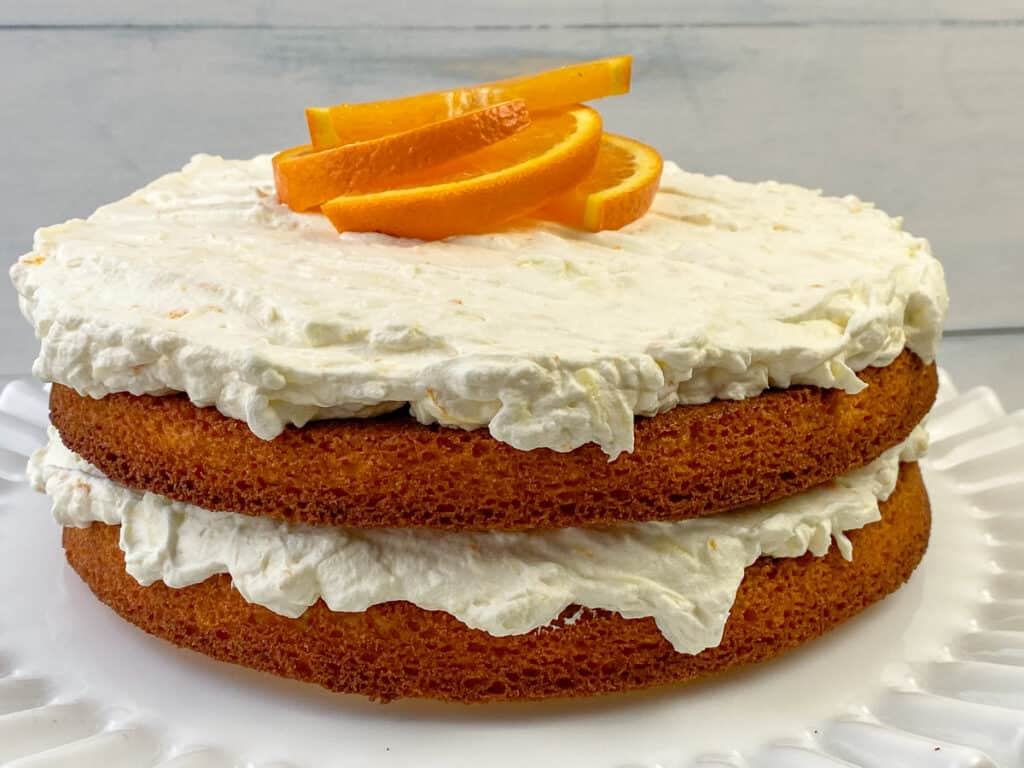 Two layers of homemade orange dreamsicle cake with frosting