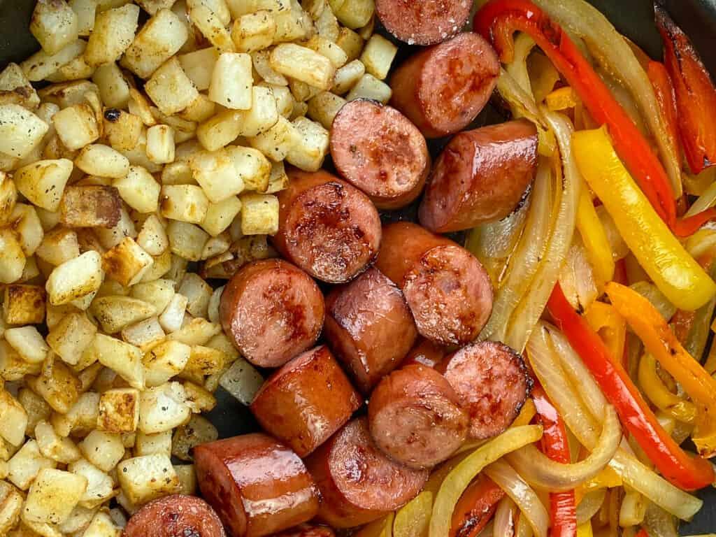 Close up Kielbasa, bell pepper strips, potatoes and onions