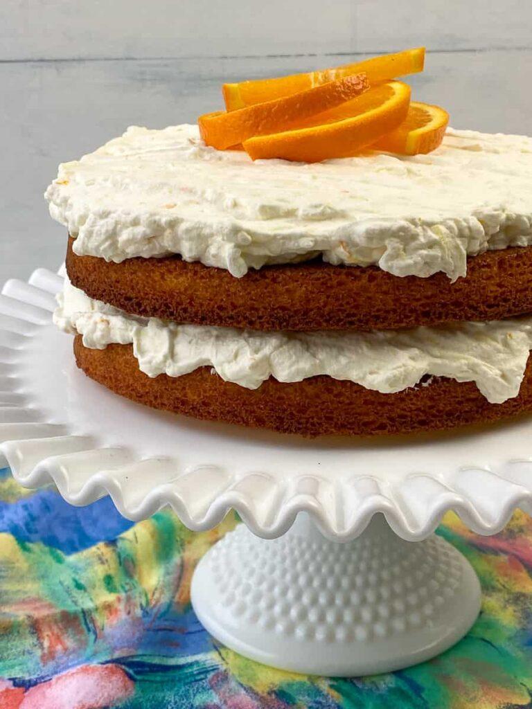 Layered Orange Dreamsicle cake on a cake stand