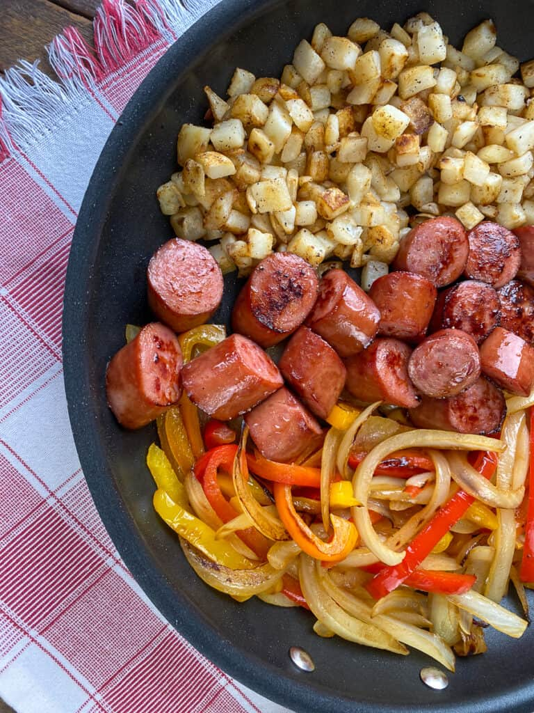 Skillet with browned Kielbasa peppers, onions and potatoes