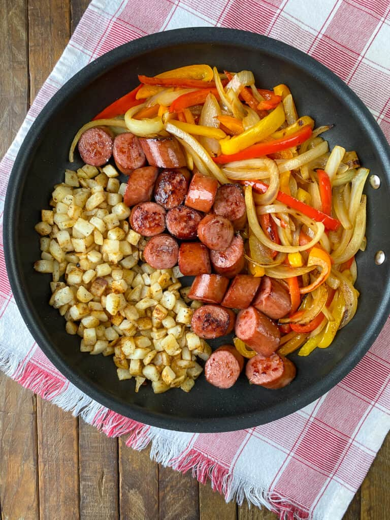Rows of Potatoes, coins of smoked sausage and strips of bell peppers and onions