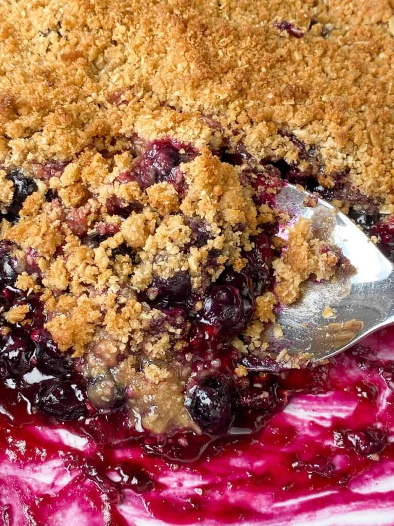 Serving spoonful of bright blueberry crisp