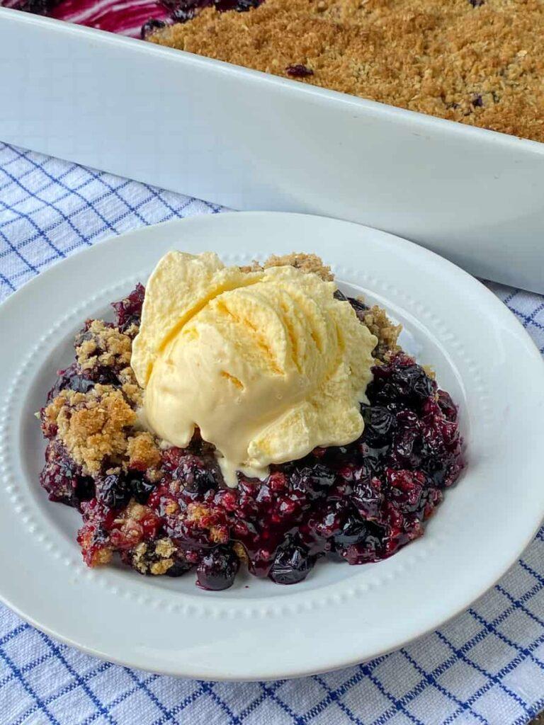 Scoop of vanilla ice cream on warm blueberry crisp