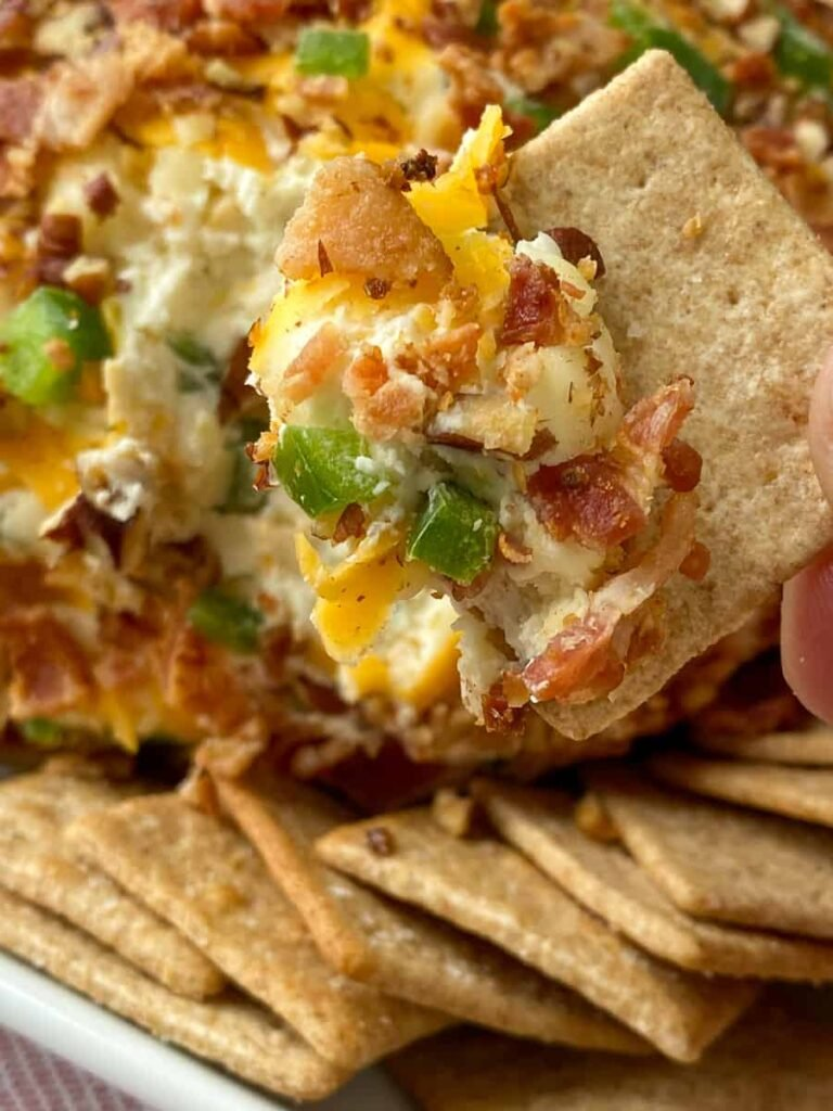 Cracker dipping in the edge of a jalapeno popper inspired cream cheese ball