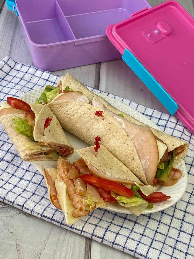 Turkey BLT wraps next to a lunch box
