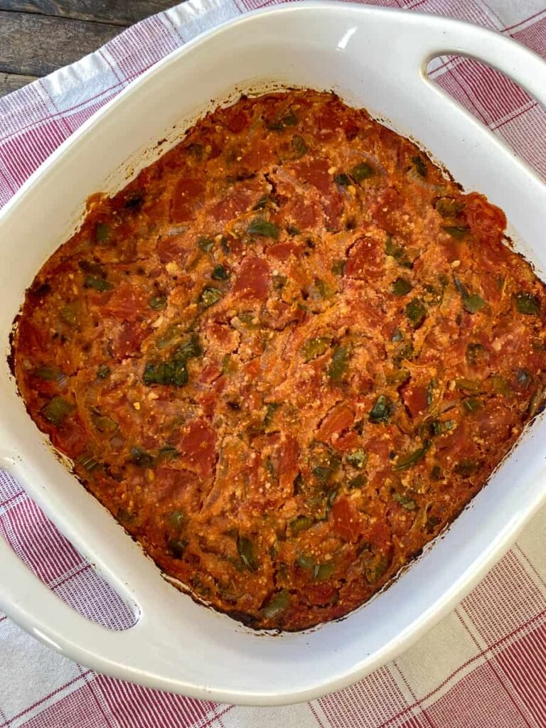 Simple baked tomato casserole on a red plaid napkin