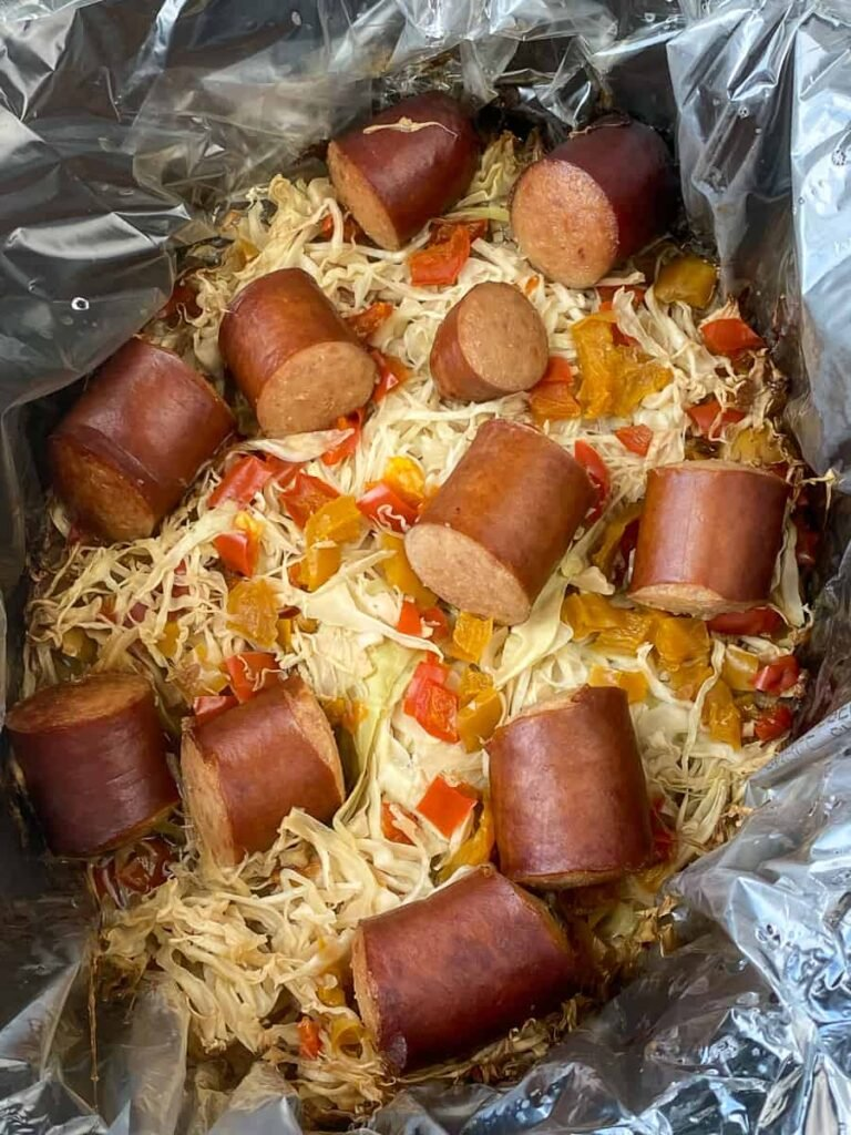 Cooked chunks of Kielbasa and cabbage in a crock pot with liner