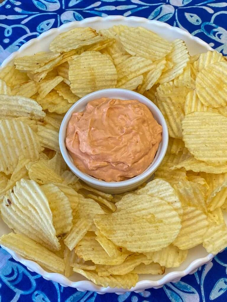 Easy chip dip in a small bowl surrounded by plain chips with ripples